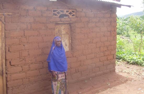 Saïdi utanför sitt hem som hon fått hjälp med att bygga genom återflyttarprojektet i Burundi.