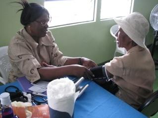En äldre dam får blodtrycket mätt under en hälsodag i Albouystown.