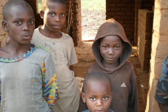 Fyra pojkar framför det hus som deras mamma, en änka med fem söner, bygger åt familjen. De kommer att få material till tak, dörrar och fönsterluckor från biståndsprojektet.